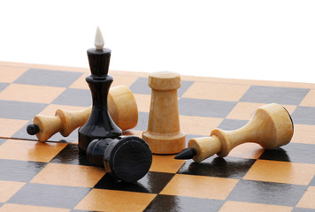 detail of wooden chessboard with several chessmen over white
