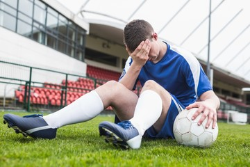 Disappointed football player in blue sitting on pitch after losi