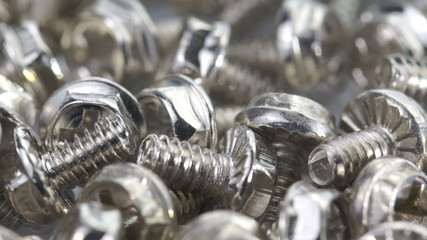 Close-up of steel bolts turning in a seamless loop