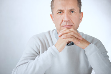 Portrait of serious middle aged businessman on gray background
