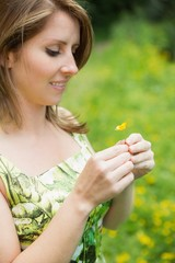 Cute woman holding flower in field