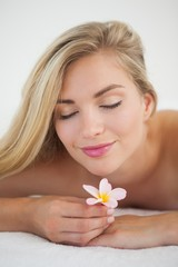 Beautiful blonde lying on massage table smelling flower