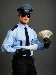 Policeman shows you money and document on gray background