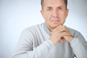 Close portrait of confident middle aged businessman with hands