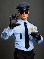 Policeman shows you stop with leather glove and holds money