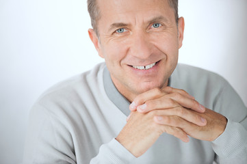 Close portrait of smiling middle aged businessman with hands