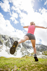Woman running and jumping in mountain