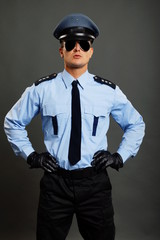 Young policemen in uniform with sunglasses standing