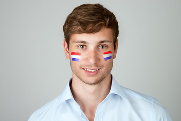 young handsome man with flag of Netherlands  painting at face