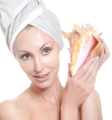 young beautiful girl in  towel on  head with a big sea shell