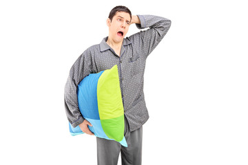 Yawning man in pajamas holding a pillow