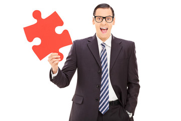 Young businessman holding a red piece of puzzle
