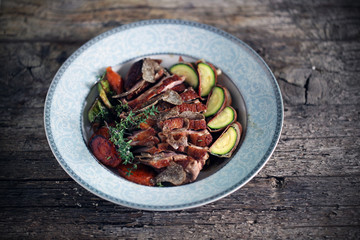 Duck breast sliced with black truffles and vegetables, thyme