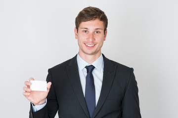 handsome businessman shows blank business card