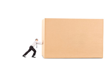 Determined businessman pushing a huge box