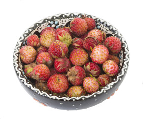 berries of wild strawberries in ceramic bowl