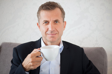 Smiling handsome man holding a cup of coffee