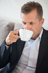 Morning portrait of handsome businessman holding coffee cup