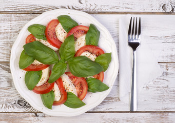 Caprese salad on wooden table top view