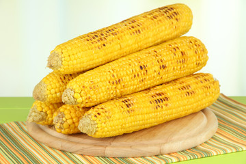 Delicious golden grilled corn on table on bright background