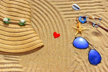 Straw hat, sun glasses and wood heart on a tropical beach
