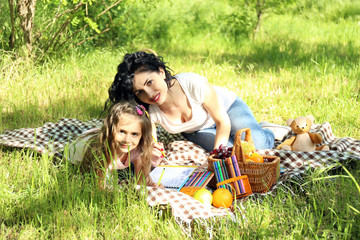 Happy mom and daughter. Picnic in the green park