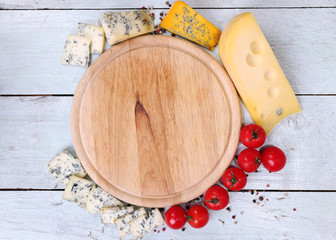 Different types of cheese with empty board on table close-up