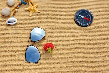 Beach scene with sun glasses, compass starfishs and one strawber