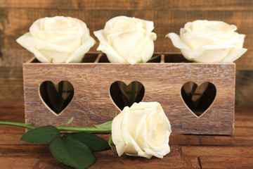 Beautiful white roses in decorative box on wooden table