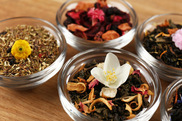 Assortment of dry tea on wooden table, close up