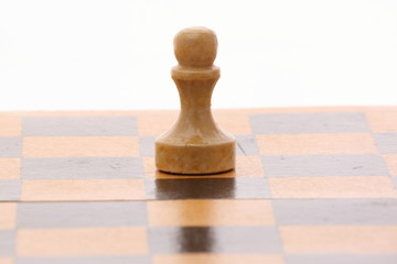 pawn on a wooden chessboard over white