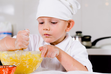 Small boy mixing ingredients for a cake in a bowl