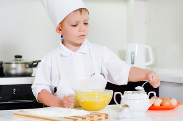 Young boy chef adding ingredients to his bowl