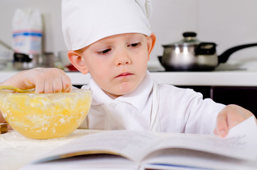 Little boy following a recipe as he bakes a cake