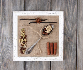 Wooden frame, vintage spoon and spices on wooden background