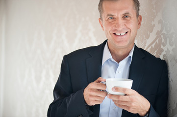 Handsome man holding cup of coffee in suit