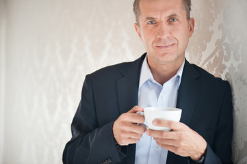 Handsome businessman holding cup of coffee and smiling