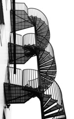 Winding metal spiral staircase, black and white image.