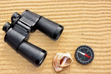 Sea Binoculars and Compass on Sand