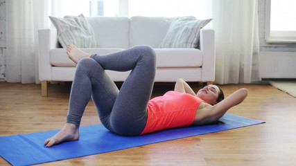 smiling girl doing exercise on mat at home