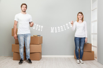 Couple unpacking surrounding boxes in a new home