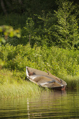 Wooden rowing boat on shore at forest lake