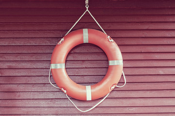 Orange life-buoy hanging on red wooden wall