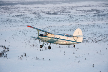 Old plane flying over the snow-covered plain