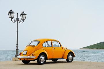 Oldtimer Käfer steht auf der Hafenmole