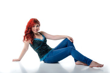 Young redhead sitting on the floor isolated on white background