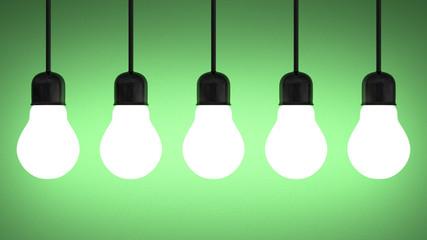 Hanging glowing tungsten light bulbs on green