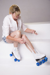 Woman fastening laces on her roller skates