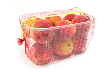 Fresh peaches in plastic bowl isolated on white