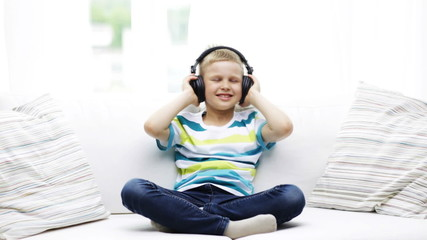 smiling little boy in headphones at home